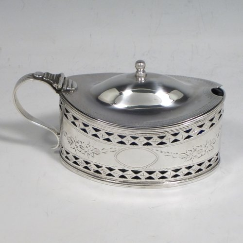 Antique Georgian sterling silver mustard pot, having an oval body with straight sides, with hand-pierced and engraved floral decoration, a hinged and domed lid with finial, a scroll handle, a blue glass liner, and all sitting on a flat base. Made by Joseph Preedy of London in 1793. The dimensions of this fine hand-made silver mustard pot are height 6 cms (2.3 inches), length 11 cms (4.3 inches), width 5 cms (2 inches), and it weighs approx. 83g (2.7 troy ounces).