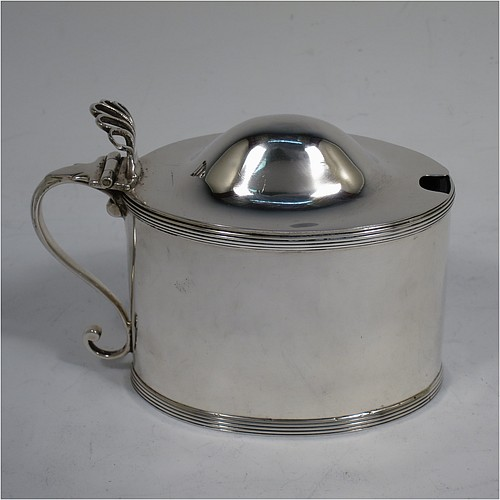 A very handsome Antique Georgian Sterling Silver mustard pot, having a plain oval straight-sided body, with applied reeded borders, a hinged domed lid with hand-pierced thumb-piece, a scroll side-handle, a blue-glass liner, and sitting on a flat base. Made by Peter and Anne Bateman of London in 1792. The dimensions of this fine hand-made antique silver mustard pot are length 10 cms (4 inches), height 7.5 cms (3 inches), and it weighs approx. 106g (3.4 troy ounces).