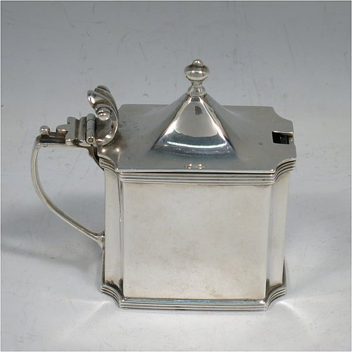 An Antique Edwardian Sterling Silver mustard pot, having a plain straight-sided body with cut-corners and applied reeded borders, a hinged domed lid with cast scroll thumb-piece and urn finial, a plain scroll handle, an original blue-glass liner, and sitting on a flat base. Made by Zachariah Barraclough & Sons of Chester in 1907. The dimensions of this fine hand-made antique silver mustard pot are length 9 cms (3.5 inches), height 9 cms (3.5 inches), and it weighs approx. 136g (4.4 troy ounces).