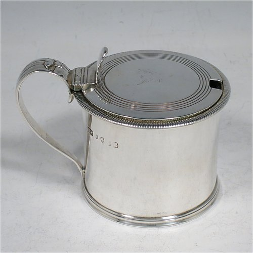 An Antique Georgian Sterling Silver drum mustard pot, having a plain round body with an applied gadroon border, a slightly domed hinged lid with a hand-engraved reeded band and a pierced thumb-piece, a scroll reeded handle with an applied anthemion leaf, and a blue-glass liner. Made by Richard Palmer I of London in 1821. The dimensions of this fine hand-made antique silver mustard pot are length 10 cms (4 inches), height 7.5 cms (3 inches), and it weighs approx. 155g (5 troy ounces). Please note that this item is crested on the lid.