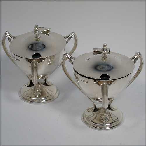 A very stylish Antique Edwardian Art Nouveau pair of mustard pots, having plain round bellied bodies, with hinged lids having cast urn finials, and three scroll side-handles attached to round pedestal feet, and with internal blue glass liners. Made by Edward Souter Barnsley of Birmingham in 1905. The dimensions of these fine hand-made antique silver mustard pots are height 8 cms (3 inches), diameter 5.5 cms (2.25 inches), and they weigh at total of approx. 164g (5.3 troy ounces).