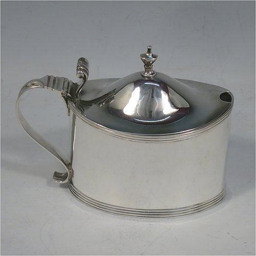 An Antique Georgian Sterling Silver mustard pot, having a plain oval straight-sided body, with applied reeded borders, a hinged domed lid with cast thumb-pieced and finial, a reeded scroll handle, a blue-glass liner, and sitting on a flat base. Made by Frances Purton & Thomas Johnson of London in 1794. The dimensions of this fine hand-made antique silver mustard pot are length 11 cms (4.25 inches), height 8.5 cms (3.3 inches), and it weighs approx. 125g (4 troy ounces).