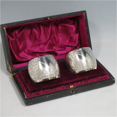 An Antique Victorian Sterling Silver pair of napkin rings, having round bellied bodies with hand-engraved floral decoration surrounding vacant cartouches, all in their original maroon satin and velvet-lined presentation box. Please note that one is engraved with Ivy, and the other with Gingko leaves. Made by Martin and Hall of Sheffield in 1893. The dimensions of these fine hand-made silver napkin rings are diameter 4.5 cms (1.75 inches), height 3.5 cms (1.3 inch), and they weigh a total of approx. 75g (2.4 troy ounces).
