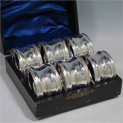 An Antique Sterling Silver set of six napkin rings, having round bodies with bellied sides and a band of hand-engraved floral work with a vacant cartouche,  and applied reed borders, all in their original dark blue satin and velvet-lined presentation box. Made by William Devenport of Birmingham in 1912. The dimensions of these fine hand-made antique silver napkin rings are diameter 5 cms (2 inches), height 3 cms (1.25 inch), and they weigh a total of approx. 132g (4.2 troy ounces).