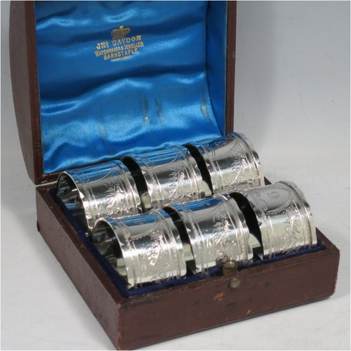 An Antique Victorian Sterling Silver set of six napkin rings, having round straight-sided bodies with hand-engraved floral decoration surrounding  cartouches numbered 1 to 6, and applied wavey-edged borders, all in their original blue satin and velvet-lined presentation box. Made by Thomas Hayes of Birmingham in 1897. The dimensions of these fine hand-made antique silver napkin rings are diameter 4 cms (1.5 inches), height 2.5 cms (1 inch), and they weigh a total of approx. 111g (3.6 troy ounces).