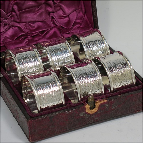 An Antique Victorian Sterling Silver set of six napkin rings, having round bodies with straight sides, hand-engraved floral decoration and vacant round cartouches, with applied plain borders, all in their original purple satin and velvet-lined presentation box. Made by Hilliard and Thomason of Chester in 1897. The dimensions of these fine hand-made antique silver napkin rings are diameter 4 cms (1.5 inches), height 2.5 cms (1 inch), and they weigh a total of approx. 113g (3.6 troy ounces). Please note that the box lock mechanism is slightly damaged.