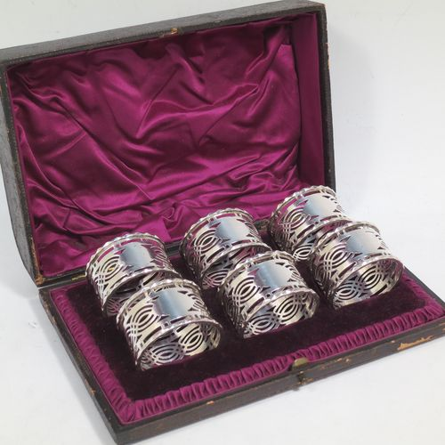 A pretty Sterling Silver set of six napkin rings, having round straight-sided bodies, with hand-pierced geometrical style decoration, a central oval vacant cartouche, and with applied faceted borders, all in their original maroon satin and velvet-lined presentation box. Made by Ferganbaum and Son of Birmingham in 1921. The dimensions of these fine hand-made silver napkin rings are diameter 4.5 cms (1.75 inches), height 2.5 cms (1 inch), and they weigh a total of approx. 140g (4.5 troy ounces).