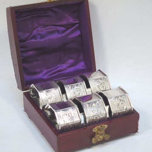 A very pretty Antique Victorian Sterling Silver set of six napkin rings, having octagonal panelled and straight-sided bodies, with hand-engraved floral and scroll decoration, with one panel as a vacant cartouche, and all in their original dark blue  satin and velvet-lined presentation box. Made by the Rolason Brothers of Birmingham in 1897. The dimensions of these fine hand-made antique silver napkin rings are width 4.5 cms (1.75 inches), height 2.5 cms (1 inch), and they weigh a total of approx. 115g (3.7 troy ounces).
