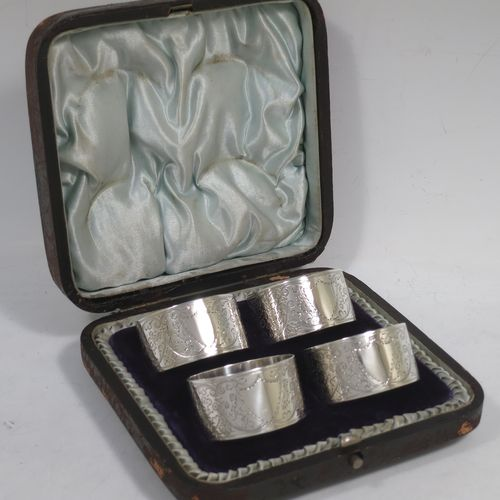 A very pretty Antique Victorian Sterling Silver set of four napkin rings, having round bodies with straight sides, hand-engraved floral and scroll decoration with two vacant shaped shield style cartouches, all in their original light blue satin and dark blue velvet-lined presentation box. Made by Walker and Hall of Sheffield in 1894. The dimensions of these fine hand-made antique silver-plated napkin rings are diameter 4.5 cms (1.75 inches), height 2.5 cms (1 inch), and they weigh a total of approx. 119g (3.8 troy ounces).