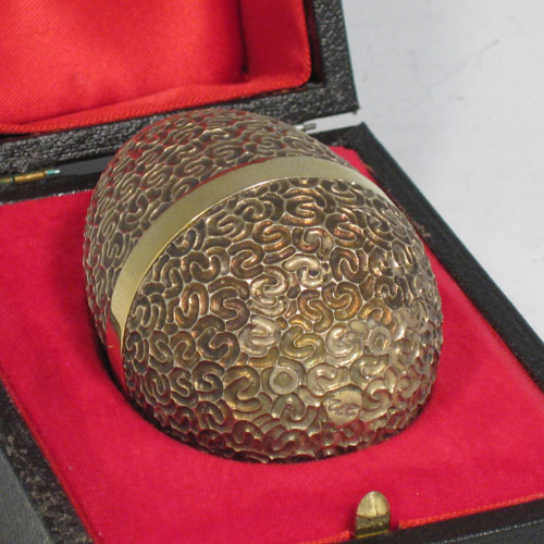 Sterling silver and gold-gilt surprise egg, made by Stuart Devlin of London in 1980. Having inside a jack-in-a-box, spring-mounted on a blue-enamelled base, with a pair of scissors and string. This has the style number 272. Height 7 cms (2.75 inches). Total weight approx. 160g (5.2 troy ounces). Please note that the presentation box in the pictures is purely for display purposes only, and this piece does NOT come with one.