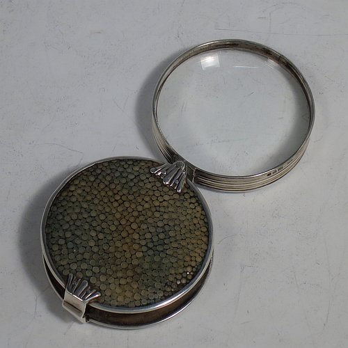 A rare Antique Sterling Silver and Shagreen magnifying glass, having a round body with pull-out and hinged magnifier, with hand-chased reeded borders, and green Shagreen covers. Made by Samuel Jacob of London in 1911. The dimensions of this fine hand-made antique silver and Shagreen magnifying glass and holder are diameter 5 cms (2 inches), length fully unfolded 11 cms (4.3 inches), and depth 1.5 cms (0.5 inch).