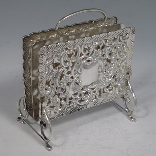 Antique Edwardian rare sterling silver letter rack in the form of a magazine holder, having hand-chased and pierced sides with floral decoration, a central divider with loop handle, and sitting on four scroll feet. Made by Synyer and Beddoes of Birmingham in 1902. The dimensions of this fine hand-made silver letter holder are height 13 cms (5 inches), width 11.5 cms (4.5 inches), depth 7 cms (2.75 inches), and it weighs approx. 168g (5.4 troy ounces).