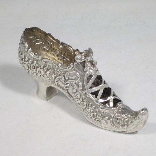 Antique Edwardian sterling silver shoe, having a hand-chased body with floral decoration, with a plain heal, and hand-pierced front laces with a bow. Made by Henry Miller of Birmingham in 1906. The dimensions of this fine hand-made silver shoe are height 5 cms (2 inches), length 11.5 cms (4.5 inches), width 3 cms (1.25 inches), and it weighs approx. 33g (1 troy ounce).