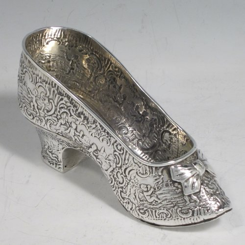 Antique Victorian sterling silver shoe, having a hand-chased body with floral decoration and scenes of winged cherubs, with a heal chased in the same style, and an applied front bow. Possibly Dutch in origin and imported into London in 1896 with full assay hallmarks. The dimensions of this fine hand-made silver shoe are height 7 cms (2.75 inches), length 14 cms (5.5 inches), width 4.5 cms (1.75 inches), and it weighs approx. 117g (3.8 troy ounces).