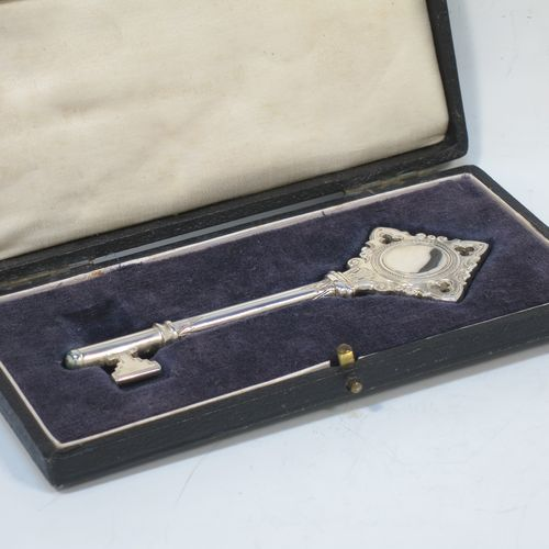 A handsome Sterling Silver 21st key to life, having a cast body with a hand-chased Gothic style handle, a plain shank, hand-chased collars, and a plain key bit, all in its original cream satin and dark-blue velvet-lined presentation box. Made by Vaughton and Sons of Birmingham in 1932. The dimensions of this fine hand-made silver 21st key to life are length 11 cms (4.3 inches) and it weighs approx. 43g (1.4 troy ounces).