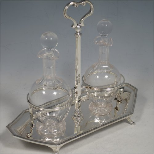 A Sterling Silver oil and vinegar set, having an octagonal boat-shaped body with applied reed-edged borders, a two-bottle frame with loop handle, a pair of hand-cut round crystal bottles with stoppers, and all sitting on four cast scroll feet. Made by Goldsmiths & Silversmiths of London in 1929. The dimensions of this fine hand-made silver oil and vinegar set are length 23 cms (9 inches), height 20 cms (8 inches), width 10 cms (4 inches), and the base weighs approx. 495g (16 troy ounces).