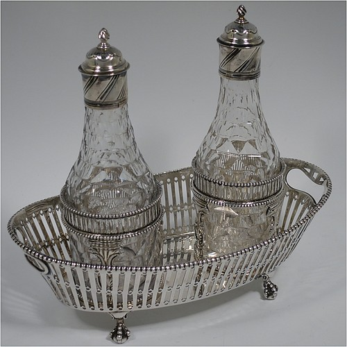 An Antique Georgian Sterling Silver oil and vinegar set, having an oval boat-shaped body with hand-pierced decoration and applied bead-edged borders, with cut-out loop side handles, a pair of hand-cut crystal bottles with stoppers in matching round galleried frames, and all sitting on four cast claw and ball feet. Made by Thomas Northcote of London in 1792. The dimensions of this fine hand-made antique silver oil and vinegar set are length 21.5 cms (8.5 inches), height (excl. bottles) 9 cms (3.5 inches), width 11.5 cms (4.5 inches), and with a total weight of approx. 400g (12.9 troy ounces). Please note that this item is crested.