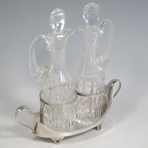 Antique Georgian sterling silver oil and vinegar set, having an oval boat-shaped body with applied bead-edged borders, two loop side handles, a pair of hand-cut crystal bottles with stoppers, and all sitting on four flange feet. Made by John Schofield of London in 1782. The dimensions of this fine hand-made silver oil and vinegar set are length 16.5 cms (6.5 inches), height (excl. bottles) 6.5 cms (2.5 inches), width 6.5 cms (2.5 inches), and the base weighs approx. 152g (5 troy ounces).