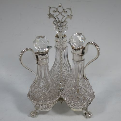 A very pretty Antique Victorian Sterling Silver oil and vinegar set, having three hand-cut crystal bottles with silver mounts, stoppers, and bead-edged scroll handles. All sitting in a hand-pierced frame with matching bead-work, a twisted central and hand-pierced handle, and all sitting on three cast claw and ball feet. Made by Martin Hall and Co., of Sheffield in 1857. The dimensions of this fine hand-made antique silver and crystal oil and vinegar set are height 19 cms (7.5 inches), width 11 cms (4.3 inches), and the frame  weighs approx. 170g (5.5 troy ounces).
