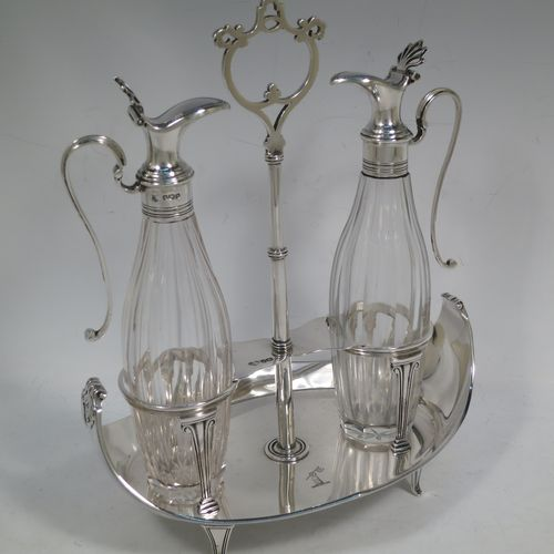 A very handosme Antique Sterling Silver oil and vinegar set in a neoclassical style, having an oval boat-shaped body with applied reed-edged borders, a two-bottle frame with hand-pierced handle, a pair of hand-cut round crystal bottles with panelled bodies and original hinged lid mounts with scroll handles, and all sitting on four flange feet. Made by Goldsmiths & Silversmiths of Sheffield in 1919. The dimensions of this fine hand-made antique silver oil and vinegar set are length 20 cms (8 inches), height 25.5 cms (10 inches), width 14 cms (5.5 inches), and it weighs approx. 250g (8 troy ounces).