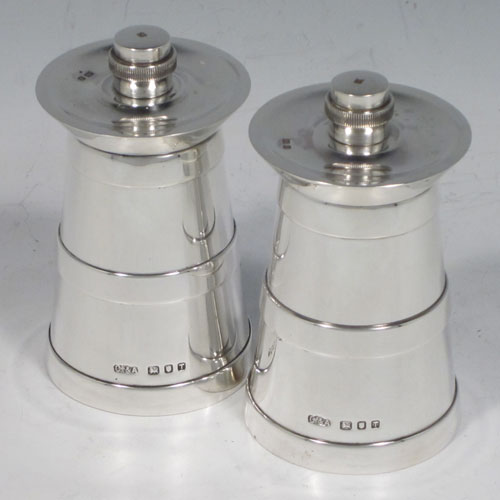Sterling silver pair of pepper grinders, having plain tapering straight sided bodies with three applied bands, with knurled grinder finials, and both having good quality grinder mechanisms that work properly. Made by Collett and Anderson of London in 1954. The dimensions of these fine hand-made silver pepper grinders are height 8 cms (3 inches), and diameter at base 4.5 cms (1.75 inches).