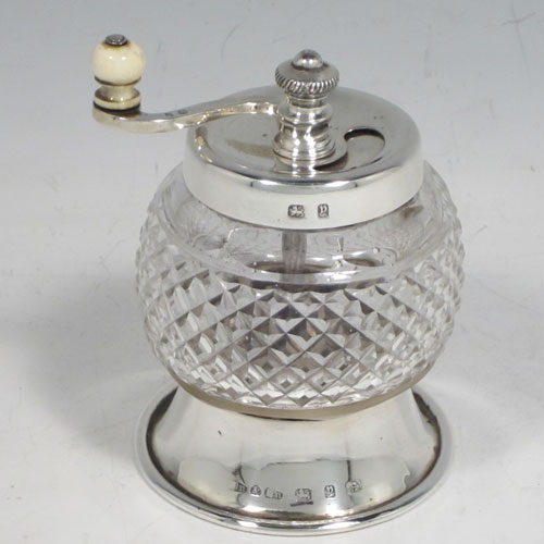 Antique Victorian sterling silver and hand-cut crystal pepper grinder, having a round body with hobnail-cut pattern, plain round mounts top and bottom, an opening for adding the pepper corns that is revealed by twisting the top mount, a side-winding grinder arm with ivory finial, and an original Peugeot grinding mechanism. Made in Birmingham in 1898. The dimensions of this fine hand-made silver and crystal pepper grinder are height 9 cms (3.5 inches), and diameter at base 6.5 cms (2.5 inches).