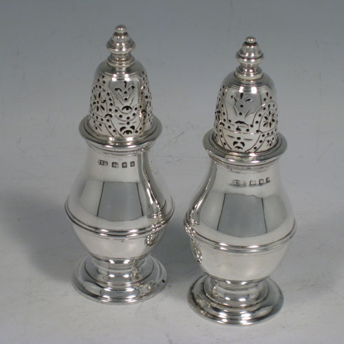 Sterling silver pair of pepper pots, in a George I style, having round plain bellied bodies with a central reeded band, pull-off hand-pierced lids with cast knop finials, and sitting on pedestal feet. Made in London in 1930/31. Height 11 cms (4.25 inches), diameter of bodies 4 cms (1.5 inches). Total weight 177g (5.7 troy ounces).
