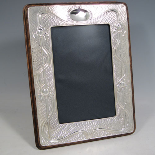 Antique Edwardian sterling silver Art Nouveau photograph frame, having a hand-made rectangular portrait body with rounded corners, a hand-chased border with lillies and reeds on a ripple patterned background, and an oval vacant cartouche, all pinned to a wood-backed easel frame. Made by A. & J. Zimmerman of Birmingham in 1903. The dimensions of this fine hand-made silver photo frame are height 18 cms (7 inches), and width 11 cms (4.3 inches).