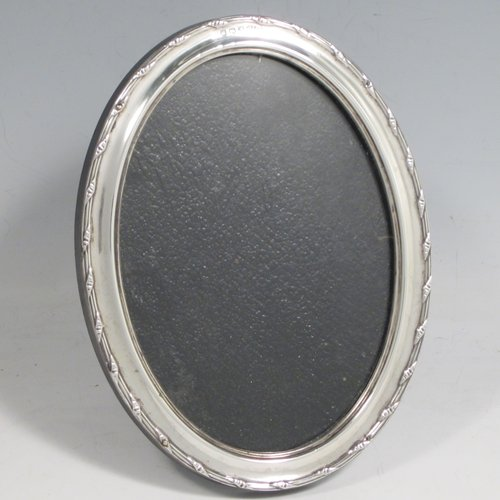 Sterling silver portrait photograph frame, having a hand-made oval body with a Ribbon and Reed border, and a black wooden easel frame. Made in Birmingham in 1926. The dimensions of this fine hand-made silver photo frame are height 13 cms (5.25 inches), and width 9 cms (3.5 inches).