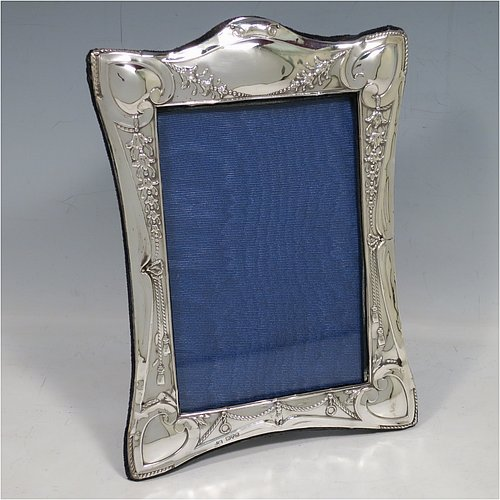 An Antique Sterling Silver Art Nouveau style photograph frame, having a shaped rectangular body, with hand-chased decoration showing flowers, swags, and heart-shaped corners, and a dark blue velvet-backed easel frame. Made by Henry Miller of Chester in 1912. The internal dimensions of this fine hand-made antique silver photo frame are 14 cms (5.5 inches) high by 9.5 cms (3.75 inches) wide.