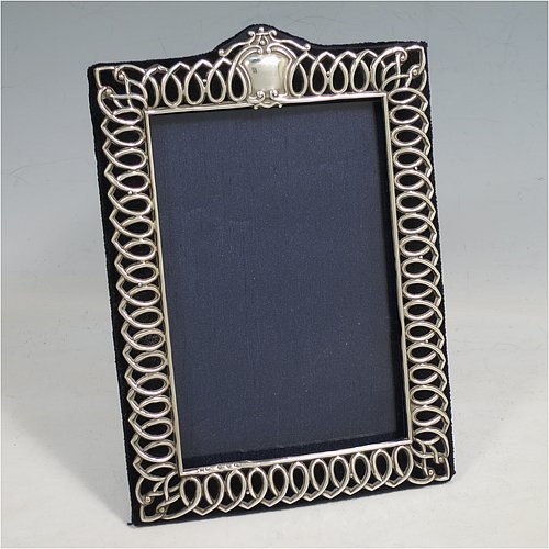 A very pretty Antique Victorian Sterling Silver photograph frame, having a rectangular aperture, surrounded by a wire-work looped border, with a top central vacant cartouche, and a dark blue velvet-backed easel frame. Made by Henry Matthews of Birmingham in 1897. The internal dimensions of this fine hand-made antique silver photo frame are 14 cms (5.5 inches) high by 9.5 cms (3.75 inches) wide.