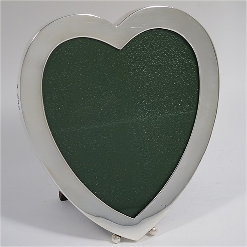 An Antique Victorian Sterling Silver heart-shaped photograph frame, having a plain square-edged border, with two ball feet, and an original wood-backed hinged easel stand. Made by James Bell and Louis Willmott of London in 1895. The internal dimensions of the heart shape are 12.5 cms (5 inches) high, and 10cms (4 inches) wide.