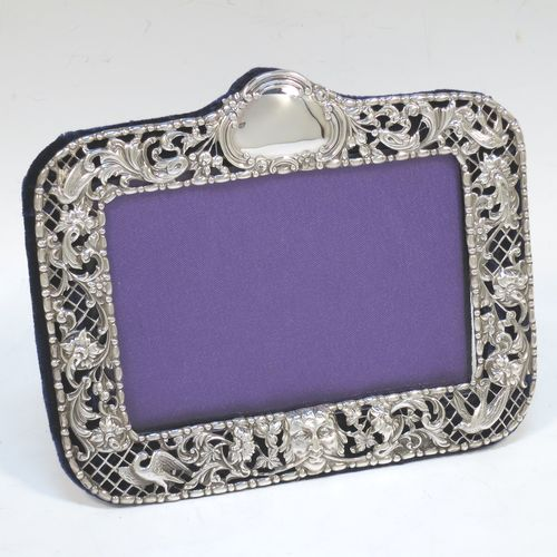 A very pretty Antique Victorian Sterling Silver photograph frame, having a rectangular landscape aperture, surrounded by a hand-pierced edge with a top vacant cartouche, pearl and bead borders, and with birds, scroll-work, and floral decoration. All pinned to a dark-blue velvet-backed easel frame. Made by William Comyns of London in 1896. The internal dimensions of this fine hand-made antique silver photo frame are 12 cms (4.75 inches) wide by 8 cms (3 inches) high.