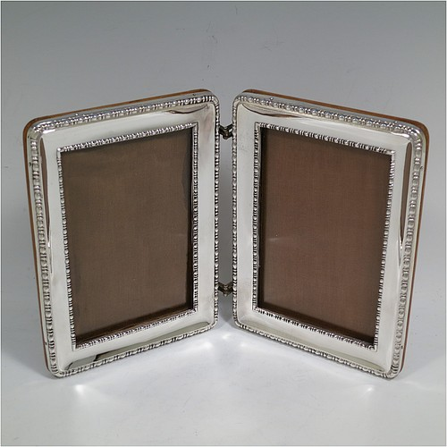 A rare and very handsome Antique Sterling Silver double hinged portrait photograph frame, having two frames with double egg and dart borders and pinned edges, with a unique double hinge mechanism that allows the photos to be shown either inwards or outwards, and with original brown wood-backed frames. Made by the Deakin Brothers of Sheffield in 1919. The internal dimensions of this fine hand-made antique silver double hinged photo frame are height 13 cms (5 inches), and width 9 cms (3.5 inches).