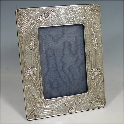 A very pretty Antique Edwardian Sterling Silver Art Nouveau style photograph frame, having a hand-chased body with Corn flowers, Wheat and Barley ears, and a Butterfly, and an original purple velvet-backed easel frame. Made by Deakin Brothers of Chester in 1903. The internal dimensions of this fine hand-made antique silver photo frame are 13 cms (5.25 inches) high by 8.5 cms (3.3 inches) wide.