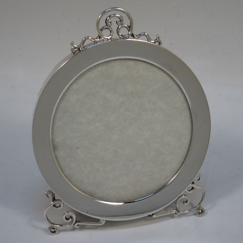 A pretty Antique Victorian Sterling Silver photograph frame, having a plain hand-made round body, an applied wire-work top mount and matching feet, and an original velvet-backed easel frame. Made by Stokes and Ireland Ltd., of Chester in 1900. The internal dimensions of this fine hand-made antique silver photo frame are diameter 9 cms (3.5 inches).