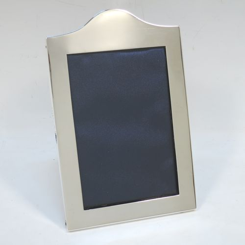 A very handsome Antique Sterling Silver portrait photograph frame, having a hand-made very plain rectangular body with pinned edges and domed upper border, and a dark blue velvet-backed easel frame. Made by William Comyns of London in 1911. The internal dimensions of this fine hand-made antique silver photo frame are height 13 cms (5 inches), and width 9 cms (3.5 inches).