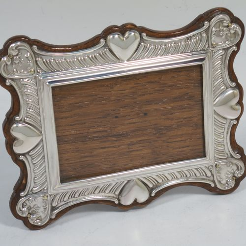 A very pretty Antique Victorian Sterling Silver photograph frame, having a rectangular aperture, surrounded by a hand-chased border with fluting, scroll-work, and four hearts decoration, and all pinned to a wood-backed easel frame. Made by the Haseler Brothers of London in 1899. The internal dimensions of this fine hand-made antique silver photo frame are 8 cms (3.25 inches) wide by 5.5 cms (2.25 inches) high.
