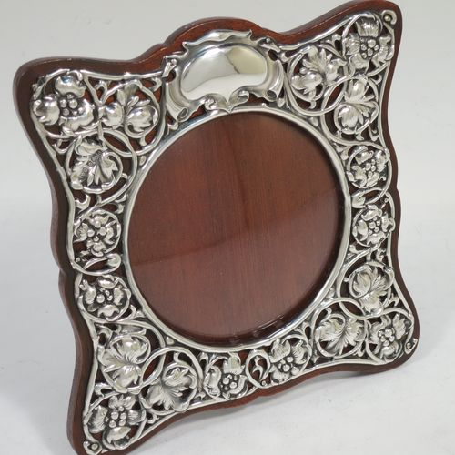 A very pretty Art Nouveau Antique Edwardian Sterling Silver photograph frame, having a round aperture with a convex glass cover, surrounded by a hand-chased and pierced border with floral and scroll decoration, and all pinned to a brown wood-backed easel frame. Made by Synyer and Beddoes of Birmingham in 1903. The internal dimensions of this fine hand-made Art Nouveau antique silver photo frame are 8.5 cms (3.3 inches) in diameter.