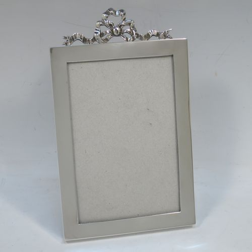 A very elegant Antique Edwardian Sterling Silver photograph frame, having a plain hand-made rectangular portrait body, an applied cast ribbon and bow top mount, and a black wood-backed easel frame. Made by the Asprey Brothers of London in 1902. The internal dimensions of this fine hand-made antique silver photo frame are height 13 cms (5 inches), by width 8.5 cms (3.3 inches).