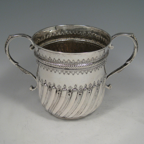 Antique Georgian sterling silver two-handled loving cup poringer with hand-chased and fluted decoration, made in London in 1756. Height 13 cms (5.25 inches), width across handles 20 cms (8inches). Weight approx. 12 troy ounces (372g).