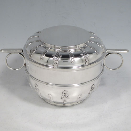 Antique Victorian sterling silver porringer and lid, having a round baluster body, a round lift-off lid, two oxe-eye side handles, all decorated with applied strap-work motifs, and sittng on a collet foot. Made by Holland, Aldwinckle, and Slater of London 1897. The dimensions of this fine hand-made silver porringer and lid are height 9 cms (3.5 inches), spread across arms 16. cms (6.5 inches), and it weighs approx. 324g (10.5 troy ounces).
