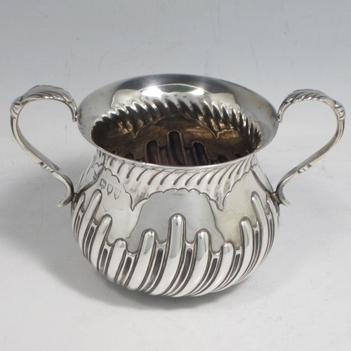 Antique Victorian sterling silver porringer, having a round baluster body with hand-chased half swirl-fluted decoration, two scroll side handles, and sitting on a flat base. Made by Robert Pringle of London in 1893. The dimensions of this fine hand-made silver porringer are height 8 cms (3 inches), spread across arms 12 cms (4.75 inches), and it weighs approx. 115g (3.7 troy ounces).