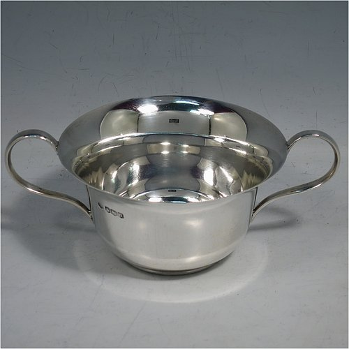 A Sterling Silver very simple porringer, having a plain round body, with two scroll side handles, and all sitting on a flat base. Made by William Hutton & Sons of Sheffield in 1918. The dimensions of this fine hand-made silver porringer are height 6 cms (2.3 inches), spread across arms 16 cms (6.3 inches), and it weighs approx. 140g (4.5 troy ounces).