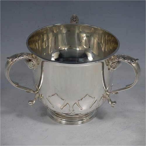 A heavy Sterling Silver three-handled porringer or loving cup, having a round body with tucked under belly and applied cut-card work, three cast scroll side-handles, and sitting on a pedestal foot. Made by Goldsmiths & Silversmiths of London in 1937. The dimensions of this fine hand-made silver loving cup or porringer are height 9.5 cms (3.75 inches), diameter 10 cms (4 inches), and it weighs approx. 417g (13.5 troy ounces).