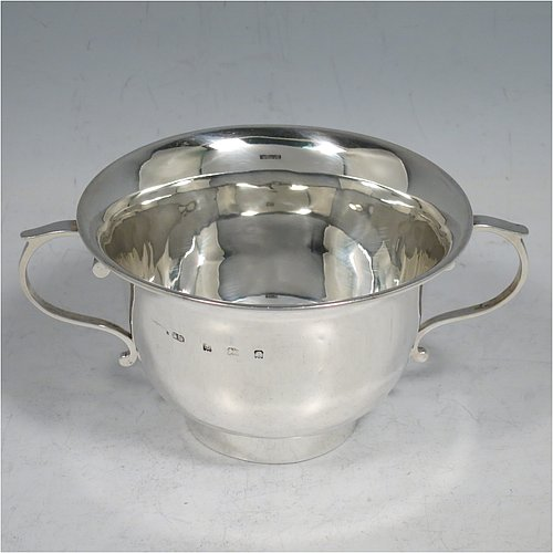 An Antique Edwardian Sterling Silver porringer, having a plain round baluster body, with two scroll side handles, and sitting on a collet foot. Made by Henry Hayes of Birmingham in 1902. The dimensions of this fine hand-made antique silver poringer are height 6.5 cms (2.5 inches), spread across arms 13 cms (5 inches), and it weighs approx. 125g (4 troy ounces).