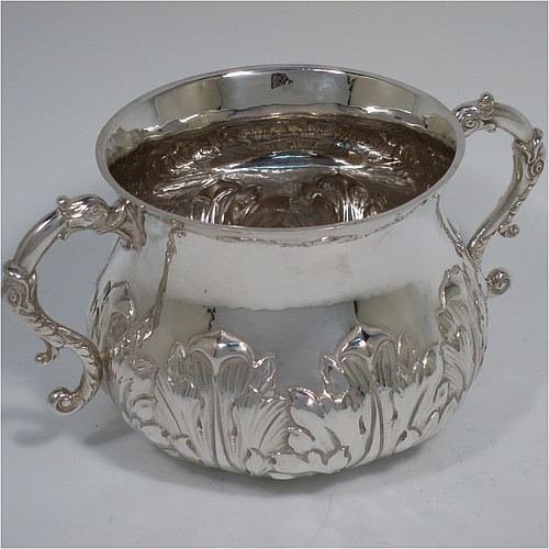A heavy Sterling Silver porringer, having a round bellied body with a slight hand-hammered finish and hand-chased anthemion and floral decoration, and two cast side-handles with stylised dolphin heads. Made by Robert Comyns of London in 1931. The dimensions of this fine hand-made silver porringer are height 7 cms (2.75 inches), spread across arms 14 cms (5.5 inches), and it weighs approx. 247g (8 troy ounces).