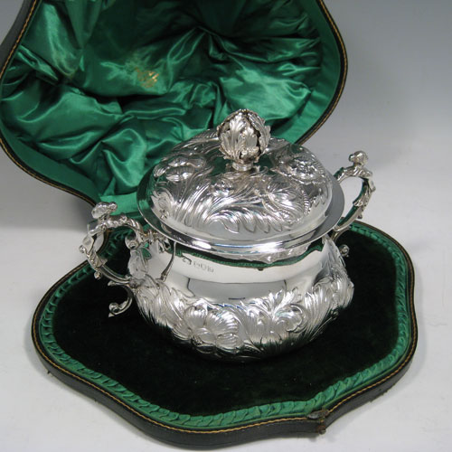 Antique Edwardian sterling silver porringer, having a round baluster body with hand-chased floral decoration, a gold-gilt interior, a lift-off lid with cast floral finial, and two cast figural handles, all in original satin and velvet-lined presentation box. Made by Carrington and Co., of London in 1907. The dimensions of this fine hand-made silver porringer and lid are height 14 cms (5.5 inches), spread across arms 19 cms (7.5 inches), and it weighs approx. 553g (17.8 troy ounces).