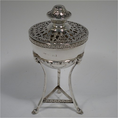 A Sterling Silver pot pourri holder, having a round bellied body sitting in a cast three-legged frame, with hoof feet, applied cast rams heads and floral borders, a pull-off lid with hand-engraved and pierced decoration surrounding a round knop handle. Made by S. Blanckensee and Sons of Birmingham in 1924. The dimensions of this fine hand-made silver pot-pourri holder are height 14 cms (5.5 inches), diameter 7 cms (2.75 inches), and it weighs approx. 147g (4.7 troy ounces).