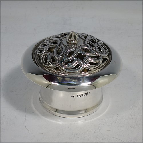 An Antique Edwardian Sterling Silver pot pourri holder, having a plain round body with tapering sides, a pull-off pierced grill with cast finial, a gold-gilt interior, and all sitting on a flat base. Made by Samuel Jacob of London in 1907. The dimensions of this fine hand-made antique silver pot-pourri holder are diameter 8 cms (3.25 inches), height 7 cms (2.75 inches), and it weighs approx. 86g (2.8 troy ounces).